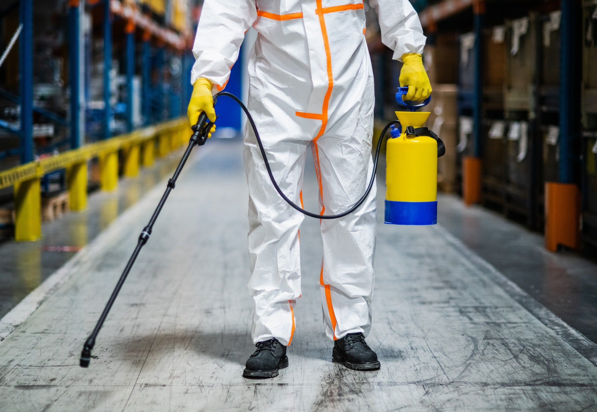 Man worker with protective mask and suit disinfecting industrial factory with spray gun